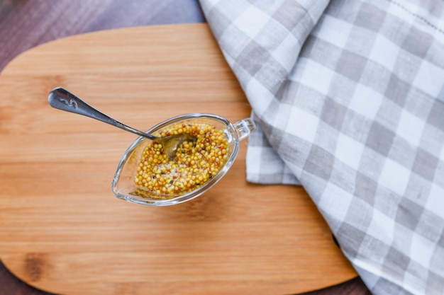 Mustard in a glass bowl. french grain mustard in a bowl. french grain mustard in a glass bowl on white wooden table