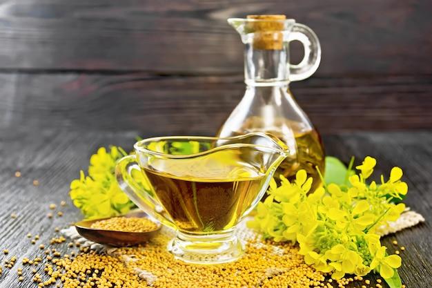 유리 그레이비 보트와 디캔터에 든 겨자 기름, 숟가락에 든 곡물, 잎, 나무 판자 배경에 있는 삼베에 노란색 겨자 꽃