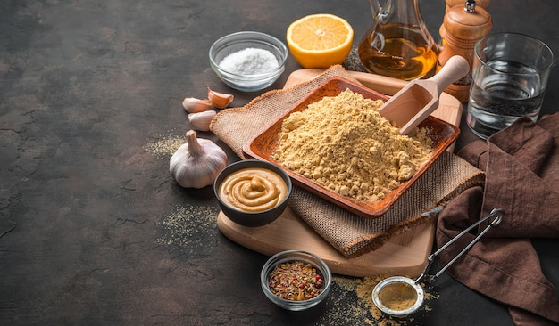 갈색 배경에 겨자 가루, 기성품 겨자, 향신료, 레몬, 마늘, 기름. 복사 공간 측면보기. 요리 개념.