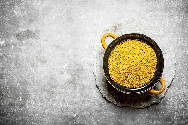 Семена горчицы в миске. на каменном столе.
