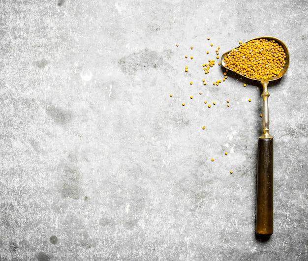 Семена горчицы в старой ложке. на каменном столе.
