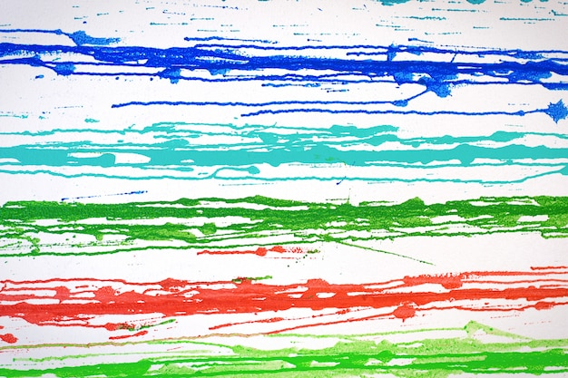 Muticolored streaks of paint leeking on white surface
