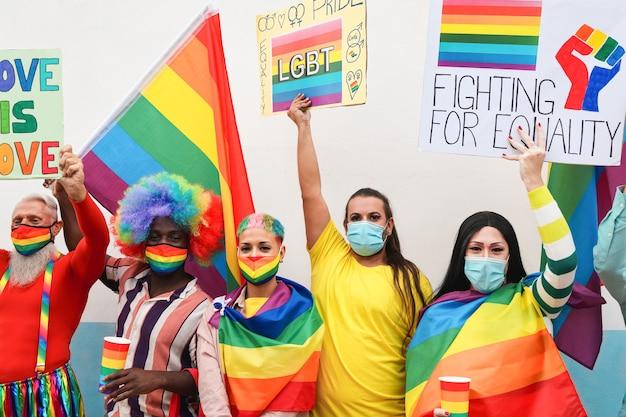 Многонациональные люди протестуют на гей-параде с транспарантами и радужными флагами лгбт в защитной маске.