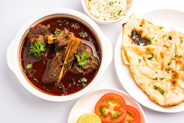 Mutton or gosht masala or indian lamb rogan josh with some seasoning, served with naan or roti, selective focus