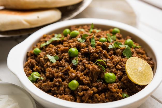 Баранина хима пав или индийский пряный фарш с хлебом или кулча, украшенный зеленым горошком. муди фон. выборочный фокус