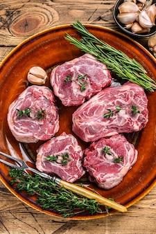 Мясо шеи баранины ягненка на деревенской тарелке с тимьяном и розмарином.