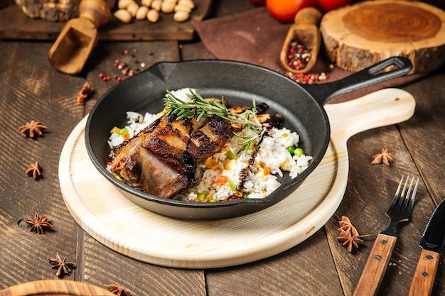 Ребрышки баранины с овощами рисом в чугунной сковороде на деревянном столе
