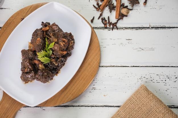 Тушеная баранина на белой тарелке и на деревянной разделочной доске традиционные индонезийские блюда