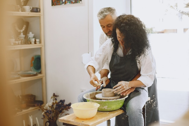 Mutual creative work. adult elegant couple in casual clothes and aprons. people creating a bowl on a pottery wheel in a clay studio.