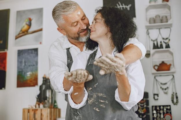 Совместная творческая работа. взрослая элегантная пара в повседневной одежде и фартуках. люди создают чашу на гончарном круге в глиняной студии.