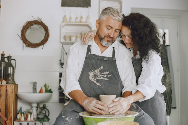 상호 창의적인 작업. 캐주얼 옷과 앞치마에 성인 우아한 커플. 클레이 스튜디오에서 도자기 휠에 그릇을 만드는 사람들.