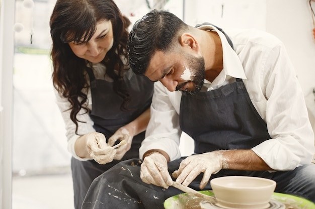 Mutual creative work. elegant couple in casual clothes and aprons. people creating a bowl on a pottery wheel in a clay studio.