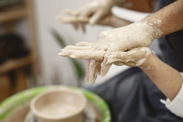 Lavoro creativo reciproco. coppia elegante in abiti casual e grembiuli. persone che creano una ciotola su un tornio in uno studio di argilla.