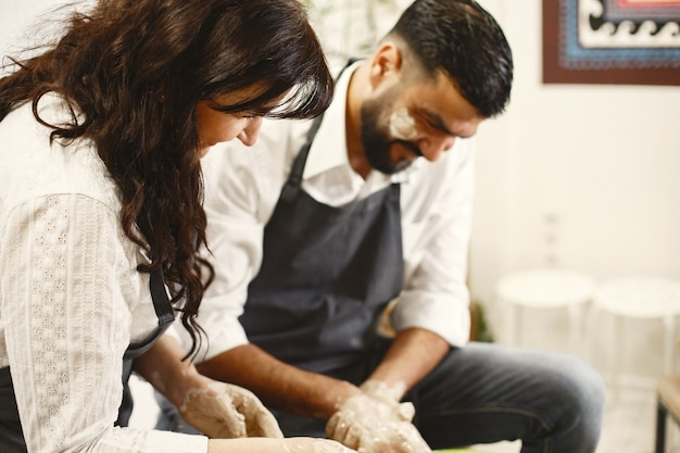 相互の創造的な仕事。カジュアルな服装とエプロンでエレガントなカップル。粘土工房のろくろでお椀を作る人。