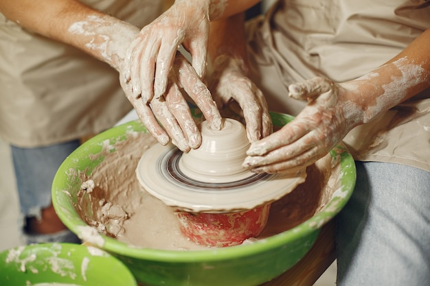 Mutual creative work. hands creating a bowl on a pottery wheel in a clay studio.