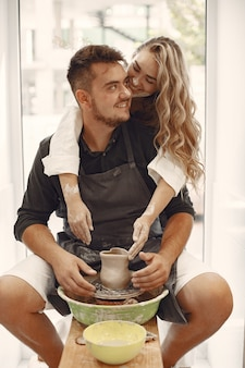 Mutual creative work. young beautiful couple in casual clothes and aprons. people creating a bowl on a pottery wheel in a clay studio.