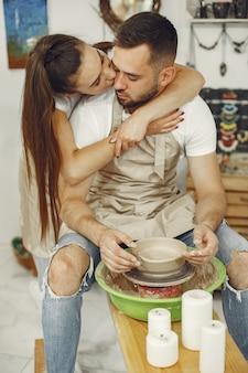 相互に創造的な仕事。カジュアルな服とエプロンの美しいカップル。クレイスタジオで陶芸のホイールでボウルを作成する人々。