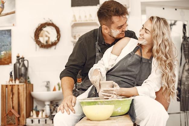 Совместная творческая работа. молодая красивая пара в повседневной одежде и фартуках. люди создают чашу на гончарном круге в глиняной студии.