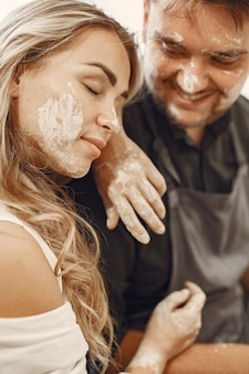 상호 창의적인 작업. 캐주얼 옷과 앞치마에 젊은 아름 다운 부부. 클레이 스튜디오에서 도자기 휠에 그릇을 만드는 사람들.