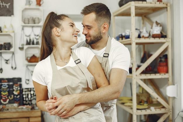 相互に創造的な仕事。カジュアルな服とエプロンの美しいカップル。人々はセラミック皿を持っています。