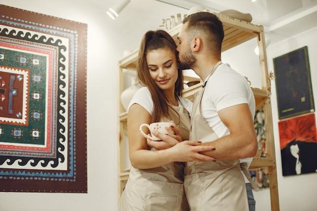 相互に創造的な仕事。カジュアルな服とエプロンの美しいカップル。人々はセラミックマグを持っています。