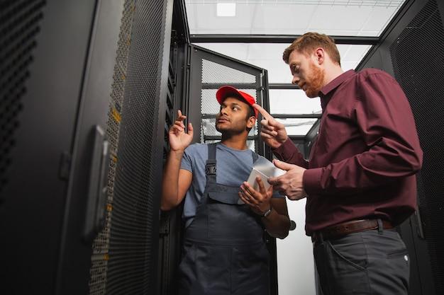 Взаимное усилие. опытные двое коллег стоят возле серверного шкафа и разговаривают