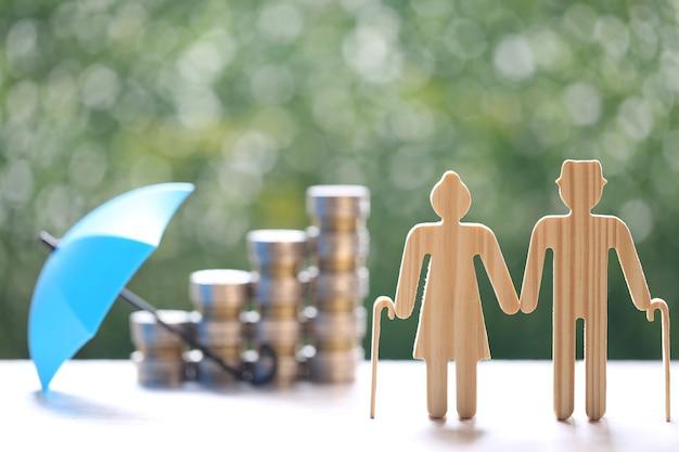 Взаимный фонд, влюбленная пара старших и стопка монет денег на естественном зеленом фоне