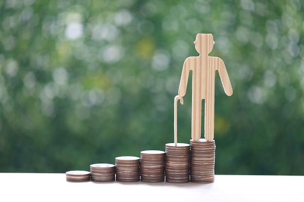 뮤추얼 펀드, 천연 녹색 배경에 동전 더미에 있는 노인, 미래 및 연금 퇴직 개념을 위한 준비를 위해 돈을 절약