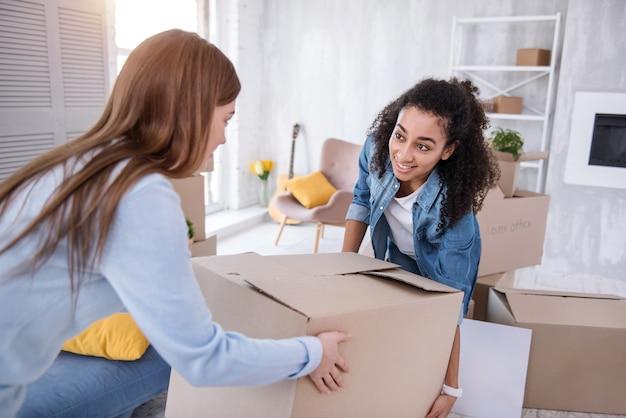 Взаимопомощь. жизнерадостные молодые девушки помогают друг другу и вместе несут тяжелую коробку, собирая вещи перед выходом из общежития.