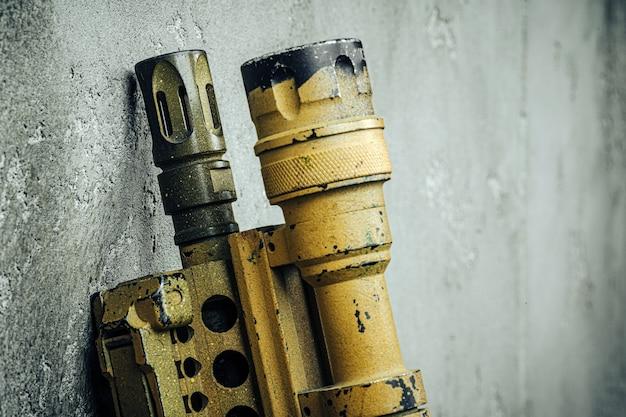 Muzzle of assault rifle against concrete wall close up