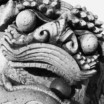 Muzzle of stone lion with ball in the mouth, bangkok, thailand. black and white image