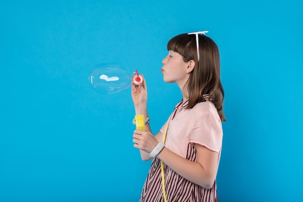 My amusement. pleased lovely girl wearing stylish clothes and blowing soap bubbles