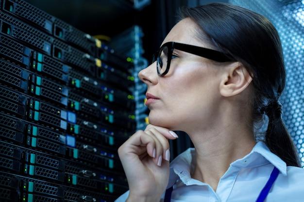 Мое внимание. сосредоточенная задумчивая женщина думает и смотрит на оборудование