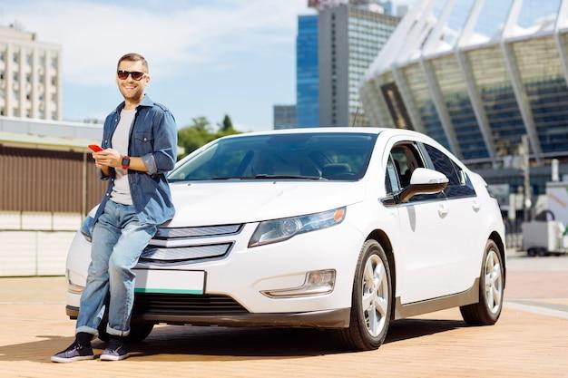 私の自動車。スマートフォンを手に持って車の近くに立っている自信のある賢い男