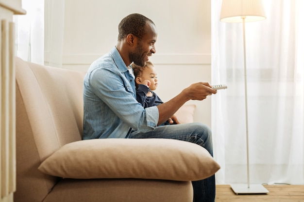 My baby. attractive smiling afro-american man holding his little son and using remote control while sitting on the couch