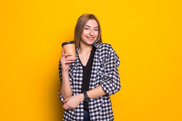 私の最高の飲み物。黄色の壁の上の手にコーヒーマグとカジュアルな服を着たかわいい若い女性