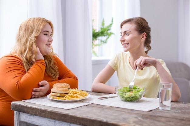 내 가장 친한 친구. 패스트 푸드를 먹고 샐러드를 먹는 그녀의 슬림 친구와 이야기하는 행복한 통통한 여자
