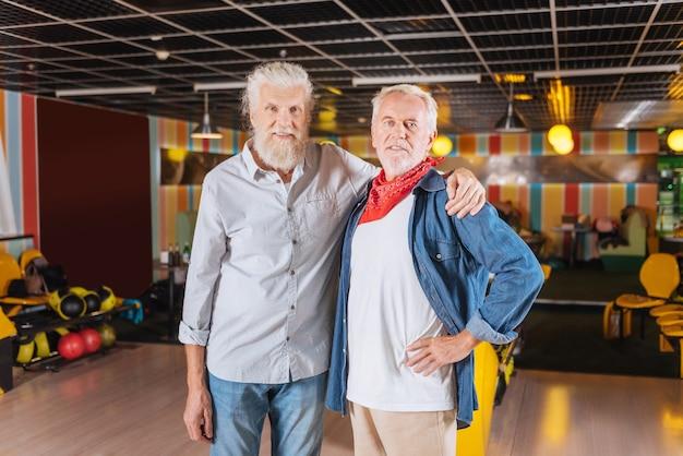 내 가장 친한 친구. 볼링 클럽에서 그와 함께 서있는 동안 그의 친구를 포옹하는 즐거운 긍정적 인 남자