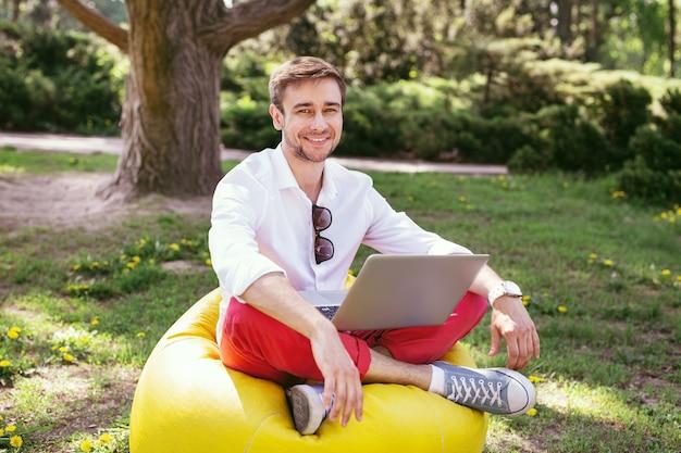 私の最高の週末。椅子に座って彼のラップトップで作業しているコンテンツの若い男