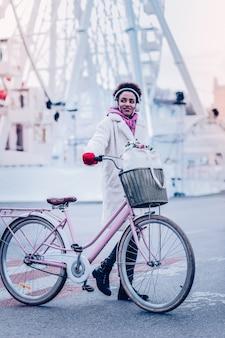 私の自転車。都心を歩きながら笑顔を浮かべて喜んでいる女性