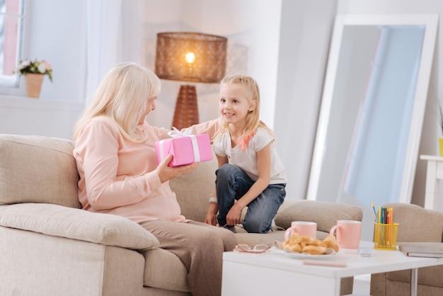내 생일. 쾌활한 좋은 노인 여성이 소파에 앉아 그녀의 손녀로부터 선물을받는 동안 행복감을 느낍니다.