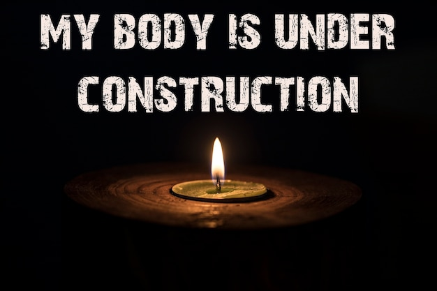 My body is under construction - white candle with dark background - in a wooden candlestick.