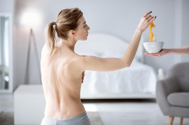 Мое тело. милая молодая женщина берет сантиметровую ленту, желая измерить параметры своего тела
