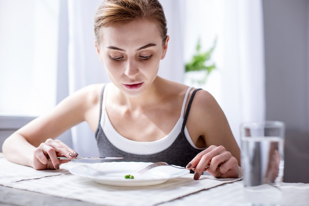 My breakfast. nice serious woman looking at the peas while holding a fork and a knife