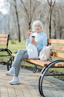 My brunch. concentrated old woman enjoying her coffee and a cookie while sitting on the bench