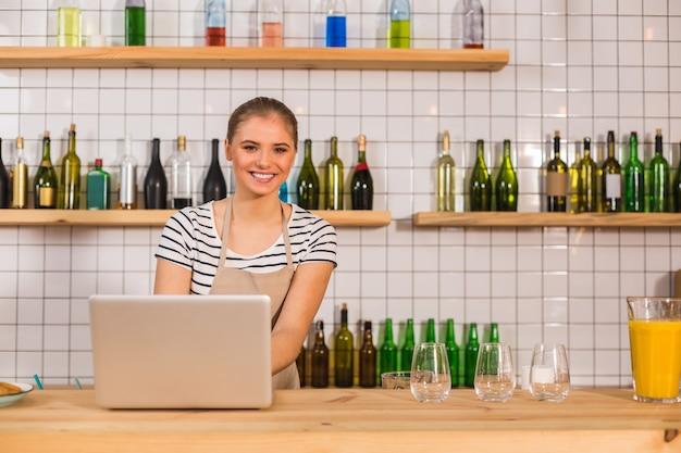 내 사업. 카운터에 서서 카페를 소유하면서 노트북에서 작업하는 기쁘게 스마트 젊은 여자