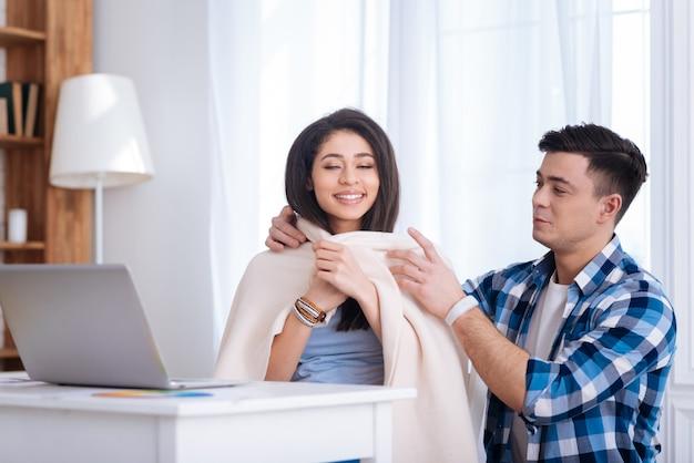 私のケア。男が彼女に毛布を置く間、椅子に座っている美しい満足のいく女性