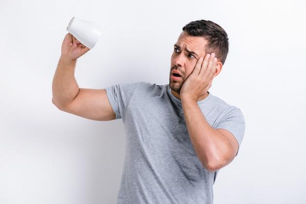 내 커피는 끝났어. 슬프게도 면도를 하지 않은 남자는 빈 컵을 뒤집고 불행해 보이고 뺨을 만집니다. 아침과 음료 개념