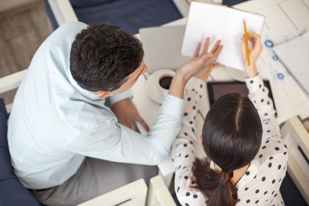 내 동료. 그 옆에 앉아 노트북을 들고있는 그의 여성 동료와 이야기하는 깔끔한 검은 머리 남자