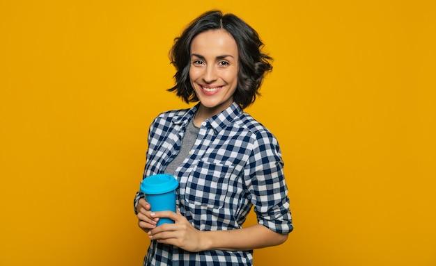 Моя удобная термокружка! молодая привлекательная студентка, небрежно одетая, улыбающаяся в камеру, повернув плечи набок, держит в себе свою любимую удобную синюю термокружку.